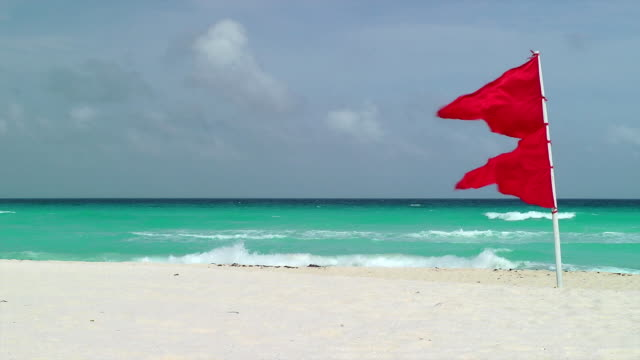 red flag waving on tropical beach - flag stock videos & royalty-free footage