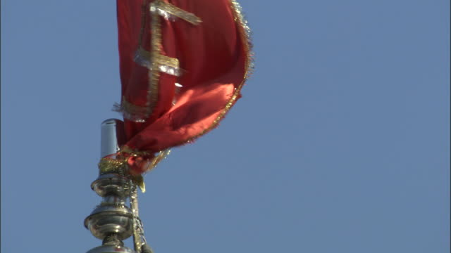 Red flag with swastika flaps in breeze, Kosi River, India Available in HD.