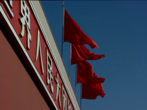 Red flags flying in breeze against blue sky pan left to portrait of Mao Forbidden City