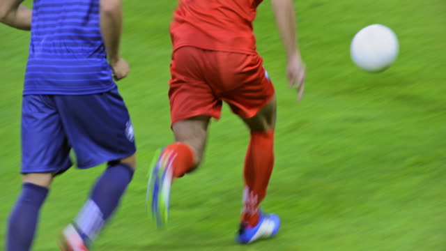 red football player shooting towards the goal - goalkeeper stock videos & royalty-free footage