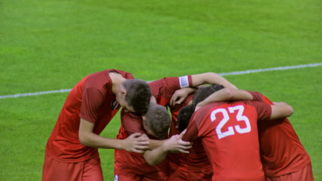 Red football team celebrating the goal at a match