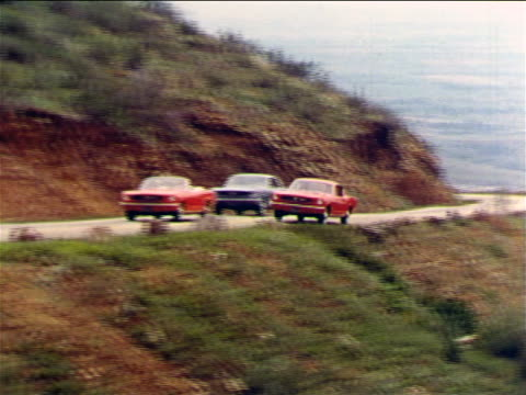 1965 PAN red Ford Mustang speeding past red convertible + blue Ford Mustangs on mountain road