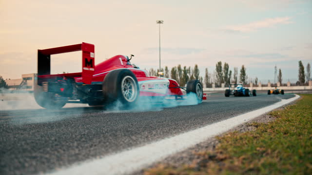 slo mo ld red formula car racing on the track and smoke coming from the tires - five people stock videos & royalty-free footage