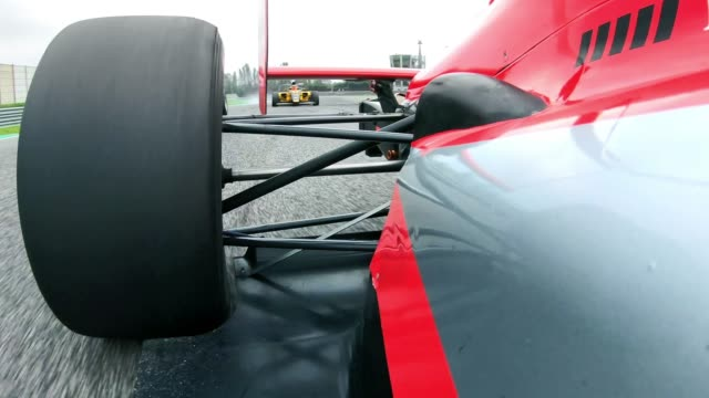 vídeos de stock e filmes b-roll de ld red formula car racing on the track being followed by other competitors - corrida