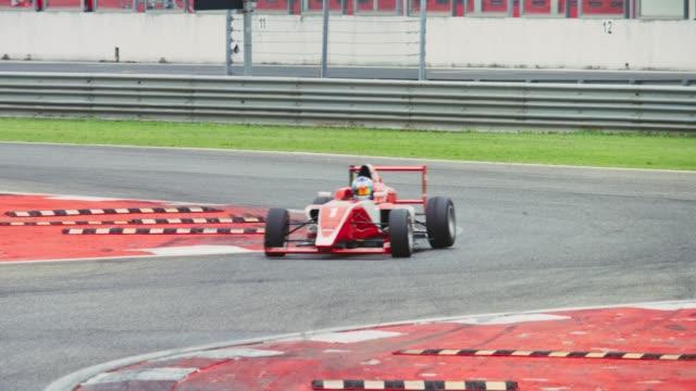 red formula car racing on the track riding through the turn - 曲線点の映像素材/bロール