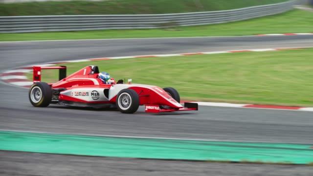 red formula racing on the track - 曲線点の映像素材/bロール