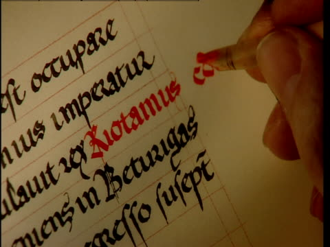 a red fountain pen is used to modify text. - kalligraphieren stock-videos und b-roll-filmmaterial