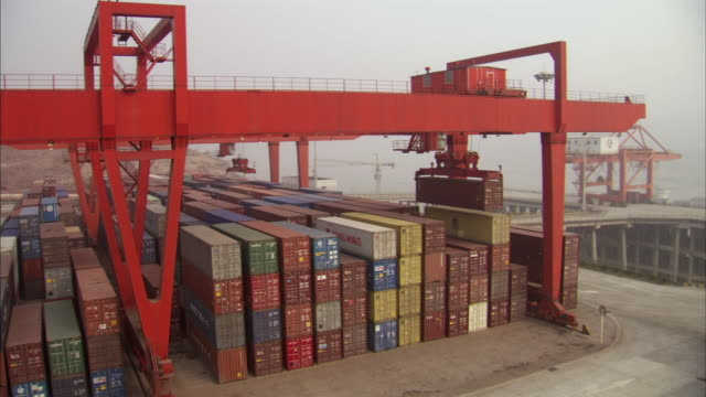 WS Red gantry crane loads containers onto huge stacks in ship / Los Angeles, California, USA