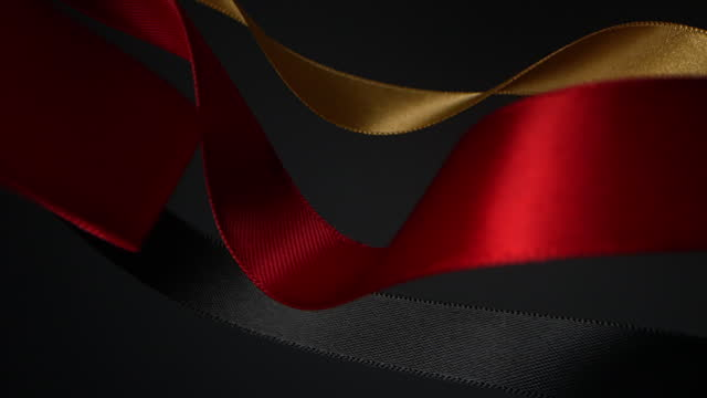red, gold and black on black background, for celebration events and party for new year, birthday party, christmas or any holidays, waiving and curling in super slow motion and close up - satin stock videos & royalty-free footage