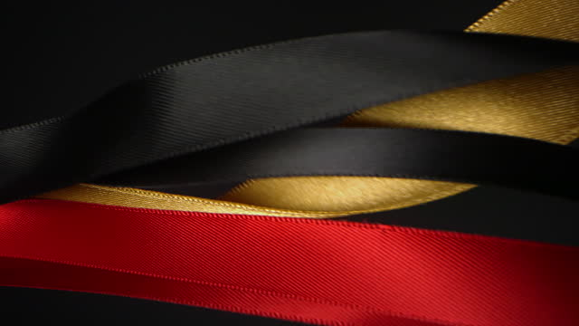 red, gold and black on black background, for celebration events and party for new year, birthday party, christmas or any holidays, waiving and curling in super slow motion and close up - anniversary stock videos & royalty-free footage