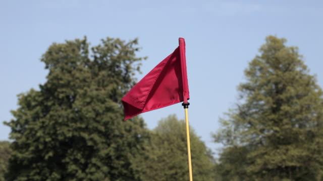 vídeos y material grabado en eventos de stock de cu red golf flag blowing in breeze with trees in background / canterbury, kent, uk - bandera de golf