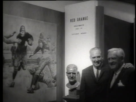 vídeos de stock e filmes b-roll de b/w red grange and other man standing by bust / football hall of fame / sound - só homens maduros