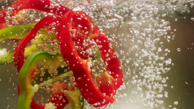 red, green and yellow bell pepper slices falling down into boiling water - green bell pepper stock videos & royalty-free footage