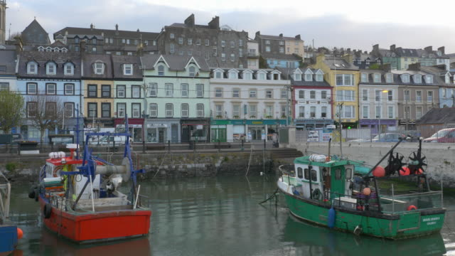 t/l red & green fishing boats in harbor, colorful village buildings, cobh, county cork, ireland - county cork stock videos & royalty-free footage