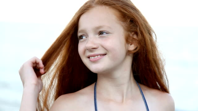 Red haired teenage girl posing, flirting against the sea