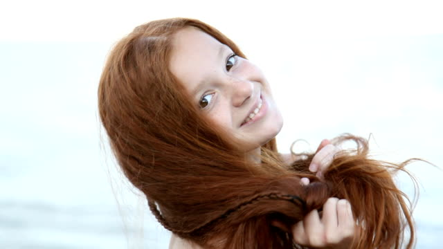 red haired teenage girl posing, flirting against the sea - long hair stock videos and b-roll footage