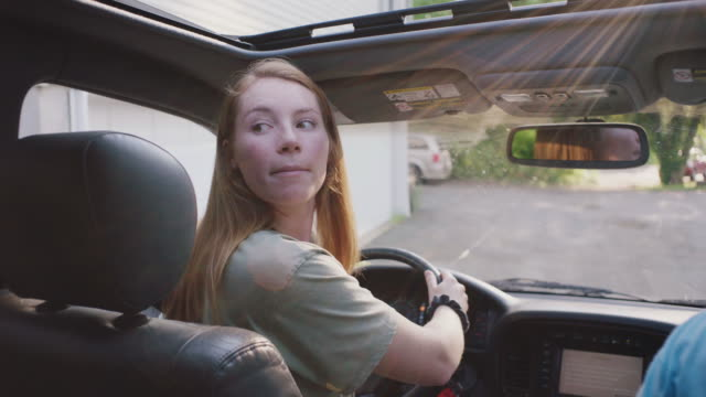 red haired woman backs car out of driveway, close up - rückwärts fahren stock-videos und b-roll-filmmaterial