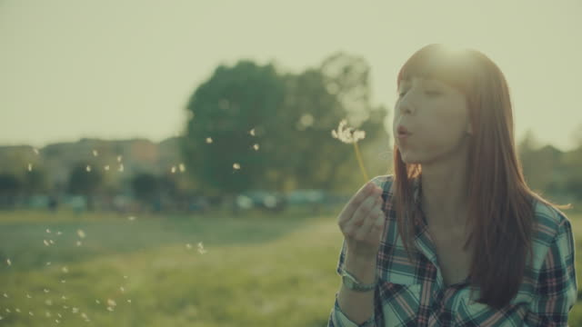 Red haired woman blows dandelion