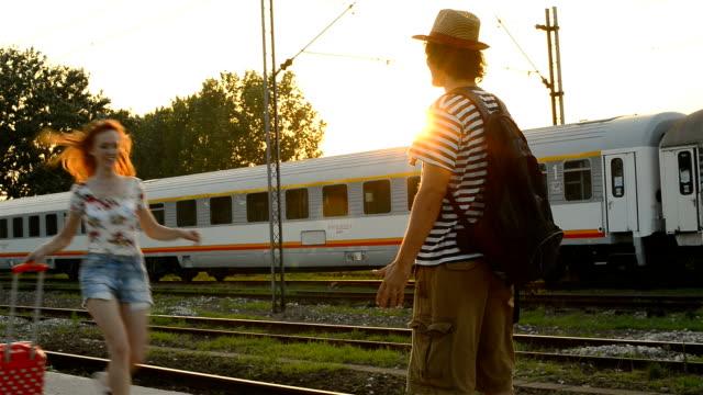 Red head woman hugs her boyfriend on train station in summer
