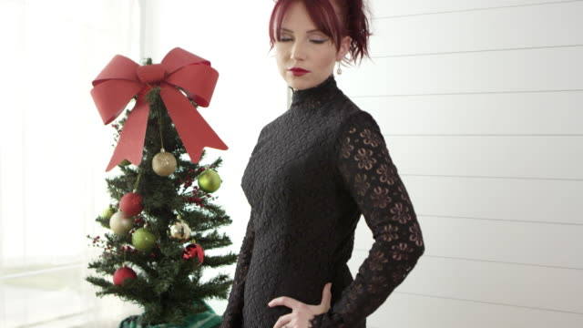 Red headed woman smiling in front of christmas tree
