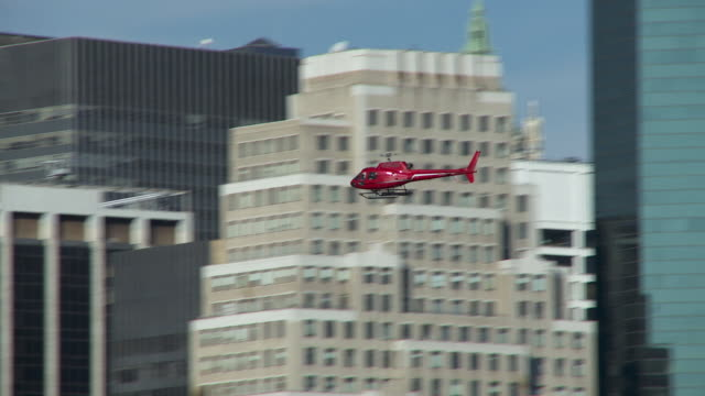 a red helicopter comes in for a landing in lower manhattan. - helicopter landing stock videos and b-roll footage