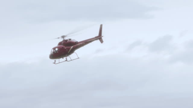 ts red helicopter flying across gray, cloudy skies - formato panoramico con bande nere video stock e b–roll