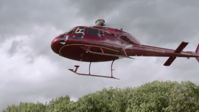 vídeos y material grabado en eventos de stock de ts red helicopter rising up and taking off near tall, leafy treetops and across dark gray, cloudy skies / united states - despegar actividad