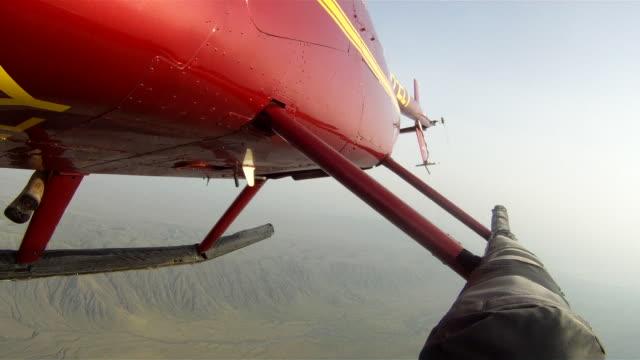 vídeos y material grabado en eventos de stock de a red helicopter turns as it flies over the ngorongoro conservation area, tanzania. - volcán activo