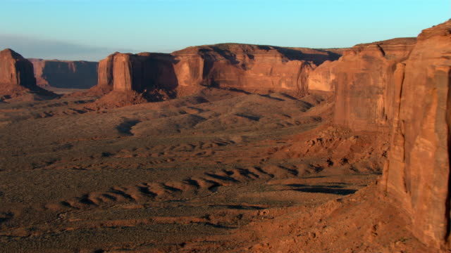 Red hills, mesas, and buttes rise above  the desert in Utah's Monument Valley Navajo Tribal Park.