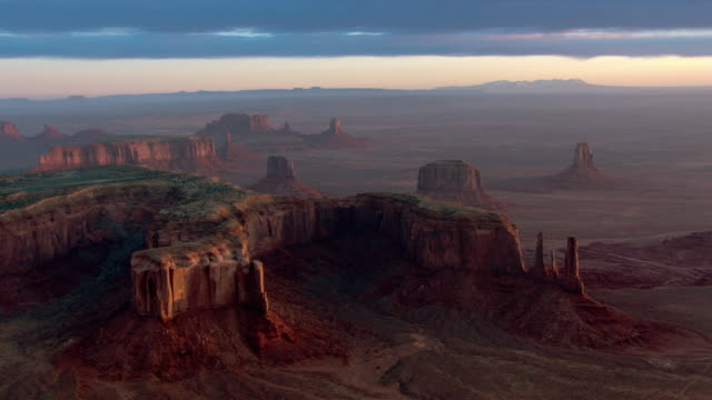 red hills, mesas, buttes, and rock formations rise above the desert in arizona's monument valley navajo tribal park. - mesa stock videos and b-roll footage