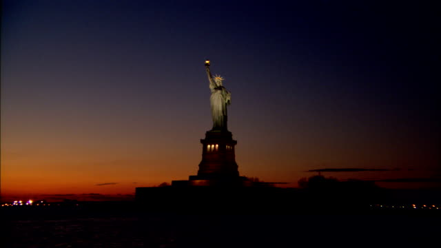a red horizon highlights the statue of liberty. - statue of liberty new york city stock videos & royalty-free footage