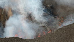 Red hot lava, gas, steam and ashes eruption from crater of active volcano