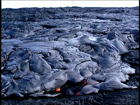 stockvideo's en b-roll-footage met red hot lava oozes from underneath hardened lava. - vaste stof