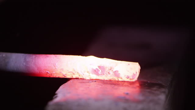 Red hot metal being hammered on anvil up close