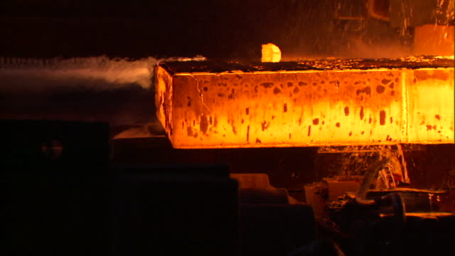 SLO MO CU PAN Red hot slab of steel on conveyor being cooled by spray of water, Beijing, China