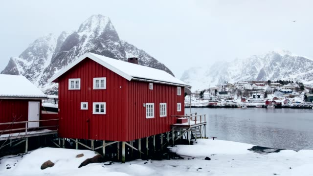 red house with snowing and mountain on arctic coastline at reine, lofoten islands, norway - arctic stock videos and b-roll footage
