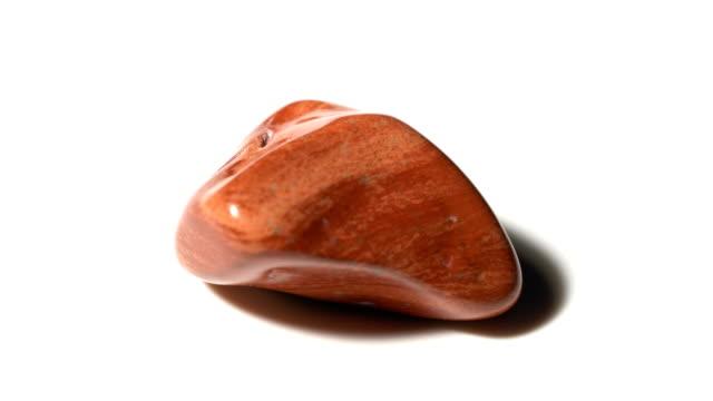 vídeos de stock e filmes b-roll de red jasper mineral stone sample in rotation with white background - jaspe mineral