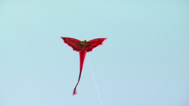 ws red kite flying in air / bali, indonesia - kite toy stock videos and b-roll footage