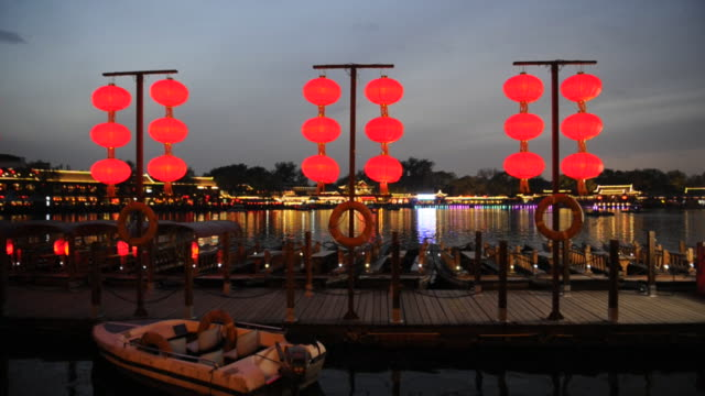Red lanterns light a dock at Lake Houhai late in the day.