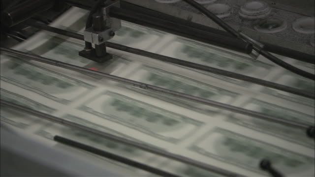 MONTAGE Red lasers scanning sheets of hundred dollar bills shooting through a printing press / Washington, District of Columbia, United States