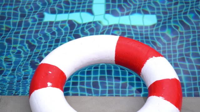 stockvideo's en b-roll-footage met rode leven boei tegen het water. rimpelingen op het water - badmeester