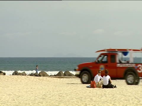 red lifeguard truck drives from right to left past two girls sitting on sandy beach ocean in background - san diego stock videos & royalty-free footage