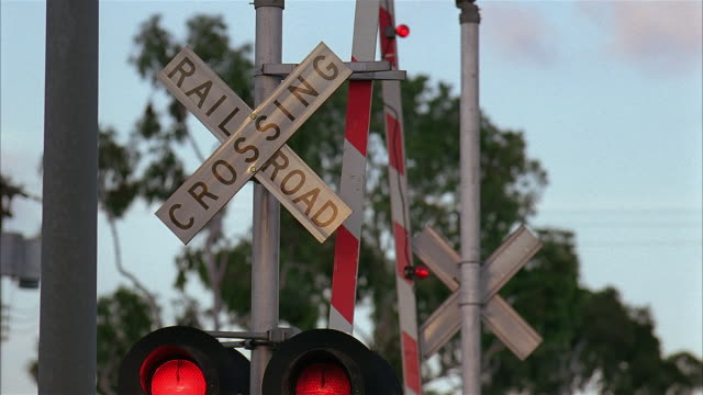 red lights flashing at railroad crossing / gate lowering down - boom barrier stock videos & royalty-free footage