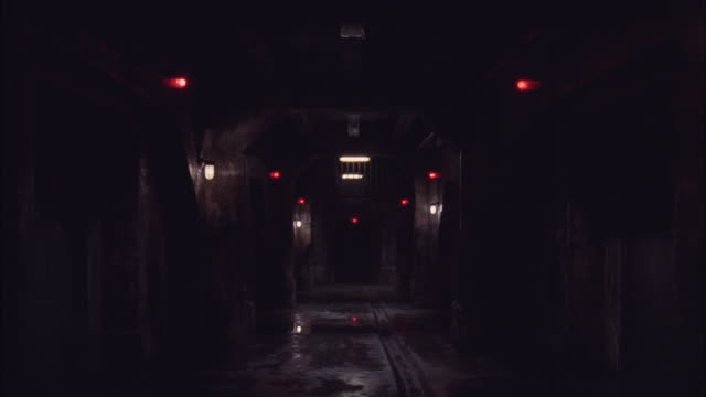 Red lights flicker above the doorways lining a dark hallway.