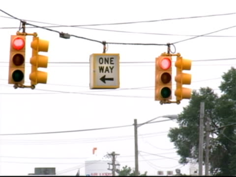 red lights on traffic signals and one way sign hanging over intersection / detroit - one way stock videos & royalty-free footage