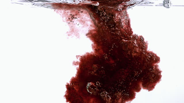ms slo mo red liquid entering into water against white background / vieux pont, normandy, france  - 化学点の映像素材/bロール