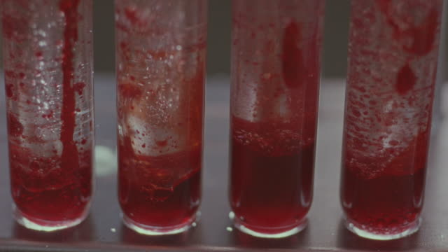 vídeos y material grabado en eventos de stock de red liquid floats in test tubes. - cuatro objetos