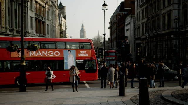 red london bases pass by with big ben and whitehall at the background - autobus a due piani video stock e b–roll