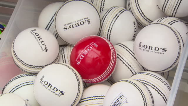red lord's cricket ball being thrown into box of white lord's cricket balls - red stock videos & royalty-free footage