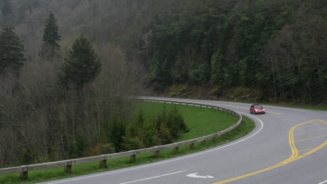 Red Mini car driving on mountain road